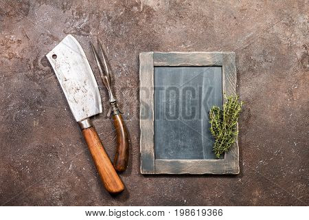 Vintage Meat cleaver, fork and chalk board on dark brown stone background