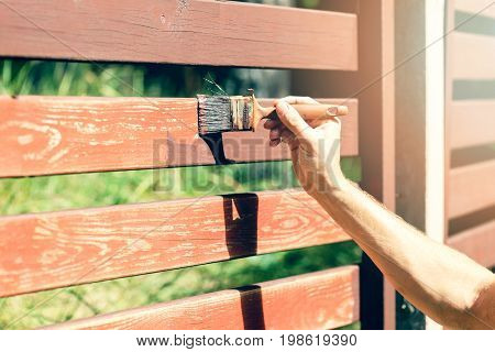 hand with paintbrush painting wooden fence with brown paint
