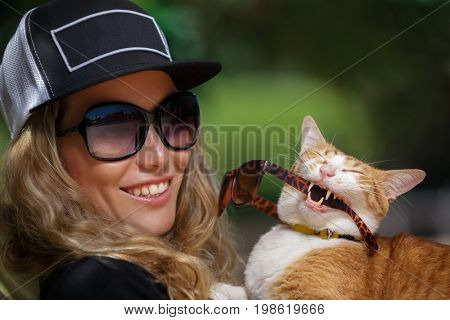A woman and a cat having fun near the outdoor swimming pool they are sunbathing