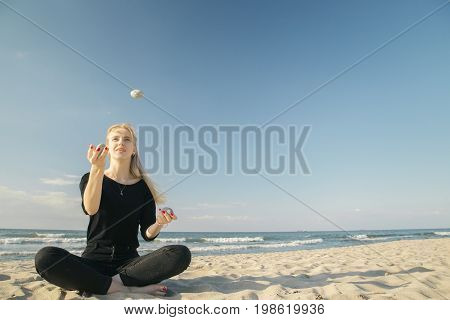 blond woman juggling pebbles at sunny sea beach