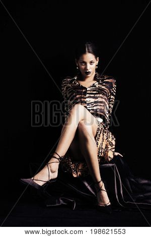 fashion shot of young beautiful black woman  in animal print skirt and shirt high heel shoes full body shot sit studio shot