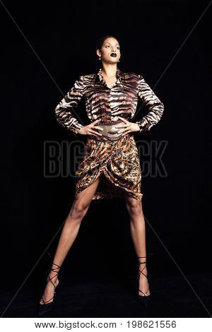 fashion shot of young beautiful black woman  in animal print skirt and shirt high heel shoes full body shot studio shot