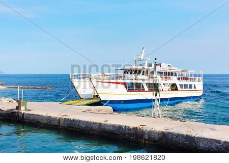 Ouranoupolis harbor in Athos, Halkidiki and ferry boat near the pier, Greece, Aegean sea