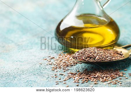 flax seeds and linseed oil in a glass jug over blue background, healthy diet with omega 3 fatty acids