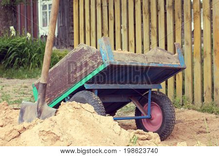 Shovel and homemade wheelbarrow to transport sand against the backdrop of a garden plot with a fence / necessary tools for work