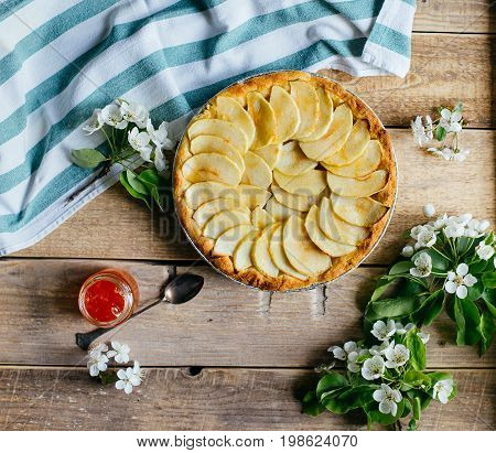 Apple pie with a blossom branch on table