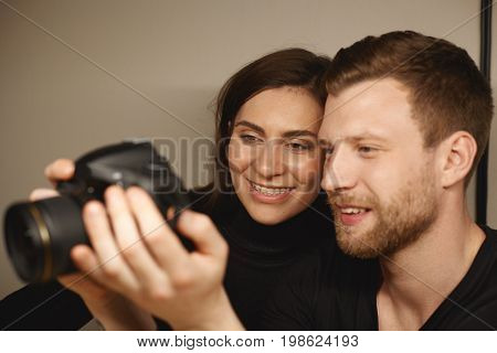 Happy l young Caucasian man and his wife holding digital camera and viewing pictures taken during honeymoon choosing good photos to get them printed. People relationships and modern technology