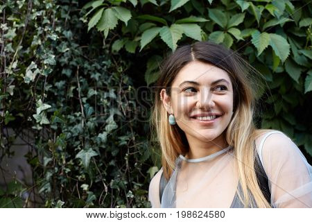 Positive cheerful teenage girl with long blonde hair wearing stylish clothes and accessories looking sideways with happy smile hiding in shadow of green wall having walk with fiends in public garden