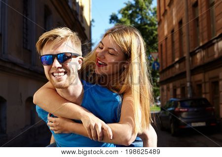 Summer lifestyle portrait of playful funny young couple enjoying good time on a date: cheerful guy with fair hair giving a piggyback ride to stunning blonde girl. Handsome husband carries his wife