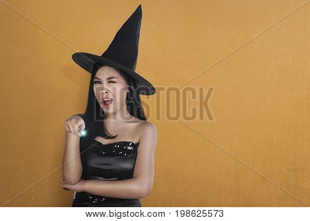 Young Asian Witch Woman In Hat Using Magic Spell