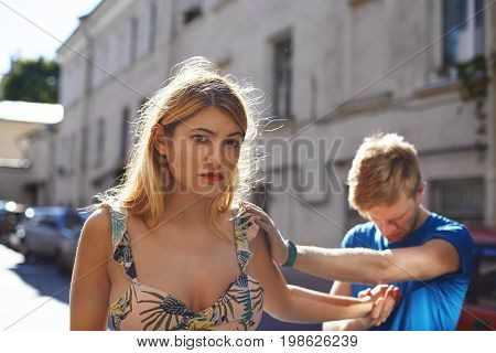 Desperate sad guy in blue t-shirt standing on street looking down and holding beautiful upset girl by the hand who is about to leave. Young couple having relationships problems has to break up