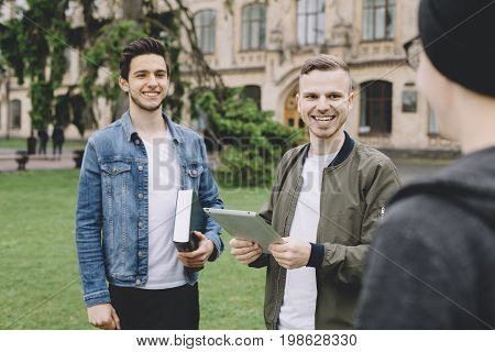 Two friends are standing outside. THeir third friend has just come to meet them so that's why these two guys are smiling. THey are happy to see their friend. Close up