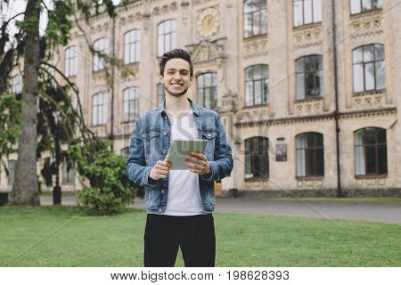 Horizontal portrait of a dark-haired guy, standing at the grass near the building where he studies. He is holding the tablet in his hands. Young man is smiling and looking at the camera. The guy is happy
