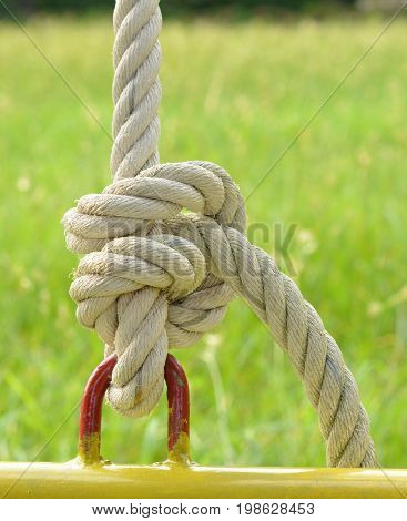 The old rope tied to steel ring with green grass background,as a symbol for relationship, harmony, engagement, teamwork or collaboration.