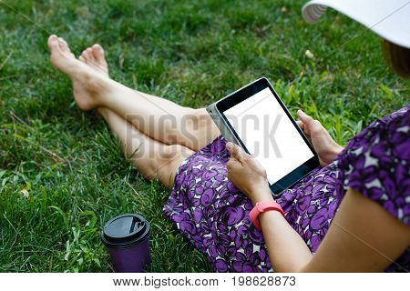 Anonymous woman in white hat and dress relaxing on green grass with tablet. Rear view. Crop shot with vertical orientation screen template.