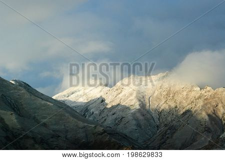 Snowy mountains in clouds in Tibet panorama view background