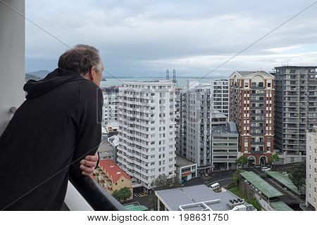 Baby boomer retired man looks at view of apartment buildings from balcony in Auckland New Zealand NZ