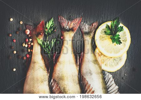 Fresh fish with aromatic herbs, spices, salt. Raw perch fish on slate tray dark vintage background, top view, healthy food, cooking, diet, nutrition concept. Freshwater fish