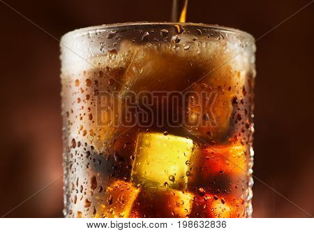 Pouring Cola with ice cubes. Cola drink with Ice and bubbles. Water drops on glass. Soda closeup. Brown background. Fizzy drink.