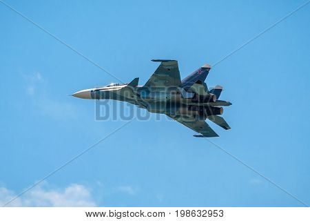 Moscow Region - July 21, 2017: Modern Russian strike fighter Su-30 flies in the blue sky at the International Aviation and Space Salon (MAKS) in Zhukovsky.