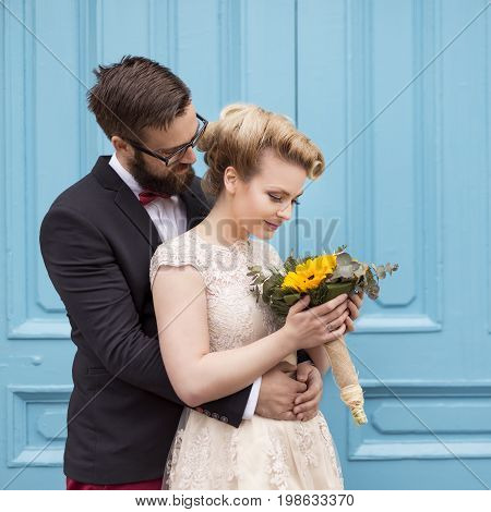 Newlywed couple standing next to a blue retro wooden door holding a sunflower wedding bouquet and hugging