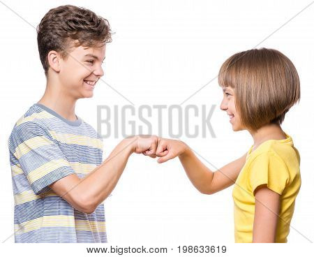 Friendship teen boy and girl are banging their fists. Portrait of happy brother and sister  fist bump isolated on white background. Funny couple children gesturing and greeting.