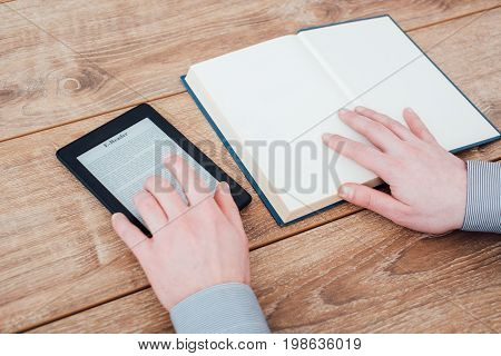 E-book Reader On A Wooden Table With Book