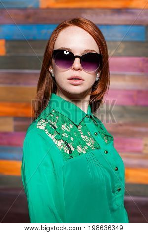 attractive redhead teen in greem blouse and sunglasses over color wooden background. beauty model woman with luxurious red hair. hairstyle