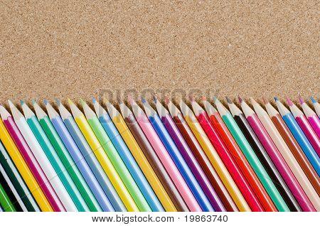 The colour pencils on ?orkboard. School concept