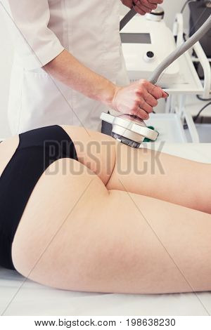 Body treatment: woman with overweight and bad skin getting rf lifting procedure to her thighs