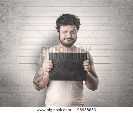 Gangster in front of a wall with table on his hand.