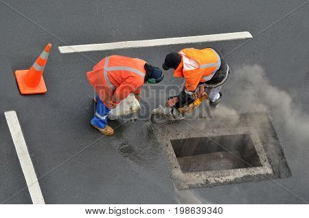 Aerial view of unrecognizable road workers cutting asphalt or concrete with saw blade at construction site