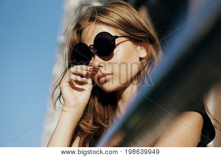 Young beautiful woman in sunglasses on the street in a megacity.