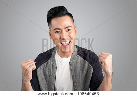 A portrait of happy winner young asian man with excited face.