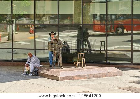 NASHVILLE TN USA - APRIL 14 2017: Chet Atkins statue. Unveiled in January 2000 the bronze statue features the artist seated on a stool playing his guitar next to an empty stool on his left waiting for a passer by to join him.