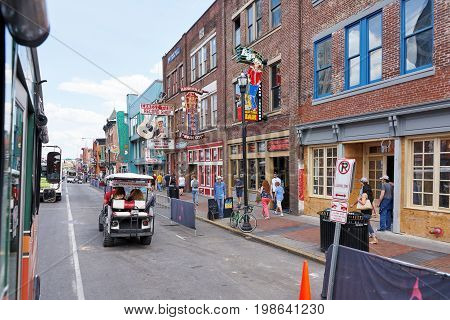 NASHVILLE TN USA - APRIL 14 2017: Nashville's historic Broadway street home to Ernest Tubb Record Shop noisy and full of bars entertainment country music and visited by countless tourists on foot in golf carts or busses.
