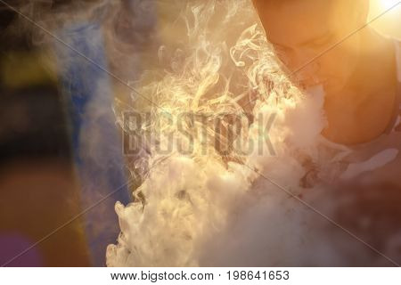 A handsome guy in military shirt is smoking ecigarette exhaling a cloud of vapor.