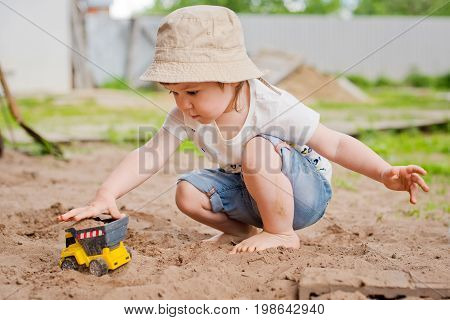 Child playing with sand on the street