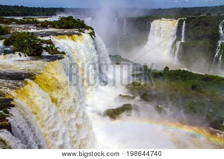Concept of active and extreme tourism. The fantastic roaring Iguazu Falls in South America, on the border of three countries: Brazil, Argentina and Paraguay