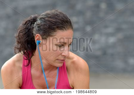 Young Woman Listening To Music As She Exercises