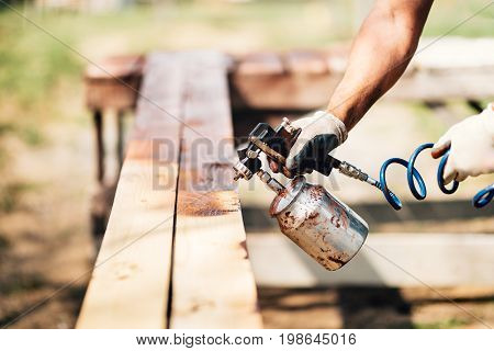 Industrial Man Painting Brown Timber Using Spray Gun And Compressor
