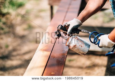 Worker Hands In Carpentry Industry. Manual Painting Of Timber With Brown Paint
