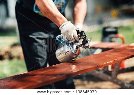 Close-up Details Of Man Using Spray Gun Or Airbrush For Painting  Fence. Carpentry Details With Wood