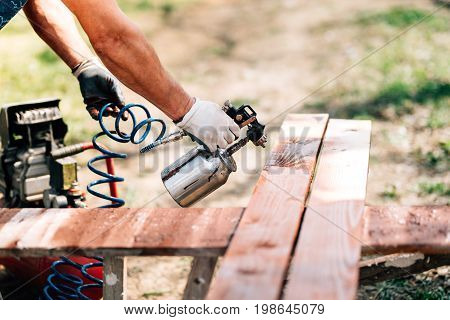 Worker Using Spray Gun For Painting Brown Timber