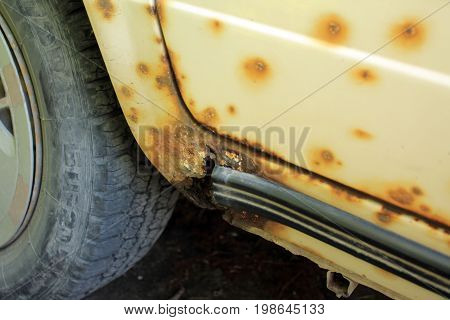Hole in threshold of old car damaged by rust and corrosion. On body are visible rust spots and damages with paint peeling.