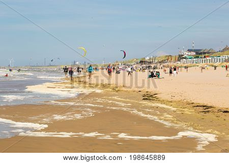 Tourists are walking along the sea line. Zandvoort is a main sea resort and touristic center