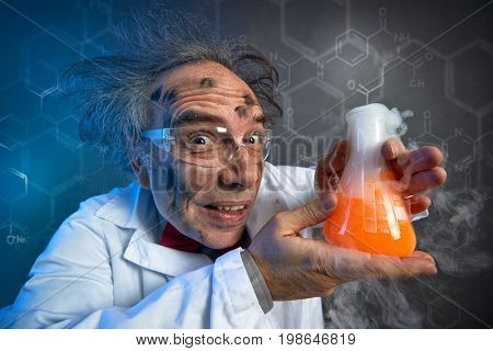 scientist with the dirty face of the explosion holding tube with chemicals