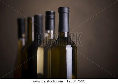 Bottles of red wine on a wooden shelf.