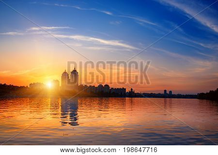 Embankment of modern european city at sunset with colorful sky. Evening at the Dnieper river in Obolon, Kiev