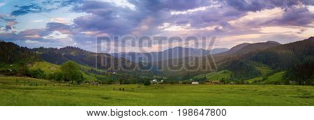 Carpathian mountains summer landscape with cloudy colorful sky and village at sunset, natural travel background